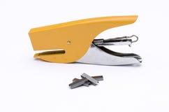 Grampeador amarelo do escritório do metal com o grampo do metal para o escritório no whit Foto de Stock