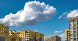 grampo do lapso de tempo 4k das nuvens de rolamento macias brancas na perspectiva dos prédios de apartamentos amarelos do multi-a filme