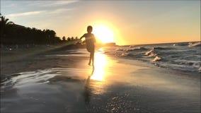 Grampo do movimento lento de um menino novo que corre em uma praia para a câmera contra um por do sol video estoque