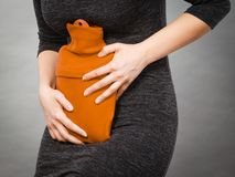 Grampos de estômago do sentimento da mulher que guardam a garrafa de água quente Fotografia de Stock