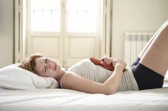 Grampos de estômago de sofrimento da jovem mulher na barriga que mantém a garrafa de água quente contra a barriga Foto de Stock