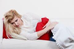 Grampos de estômago do sentimento da mulher que encontram-se no cofa Imagem de Stock