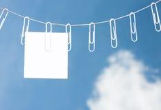 Grampos de papel em uma corda com uma nota imagem de stock