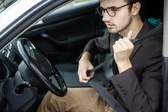 Grampos do homem novo em sua correia Está sentando-se em seu carro Conceito da segurança de estrada foto de stock