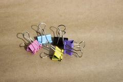 Grampos para o papel de cores diferentes no fundo do papel de embalagem marrom áspero stationery fotos de stock royalty free