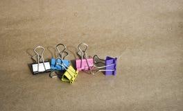 Grampos para o papel de cores diferentes no fundo do papel de embalagem marrom ?spero stationery foto de stock royalty free