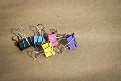 Grampos para o papel de cores diferentes no fundo do papel de embalagem marrom ?spero stationery fotos de stock royalty free
