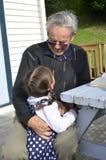Gran abrazo del abuelo su biznieto foto de archivo