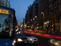 Gran através dos carros e de ônibus moventes durante o por do sol Imagens de Stock