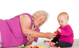 Gran babysitting her small grandchild. Elderly grandmother lying on the floor babysitting her small grandchild as the two play contentedly together with toy stock photos