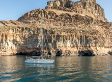 Gran Canaria, Canary Islands in Spain: Sailboat at rest in the ocean in front of mountains at the coast at Puerto de Stock Image