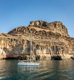 Gran Canaria, Canary Islands in Spain: Sailboat at rest in the ocean in front of mountains at the coast at Puerto de Stock Photos