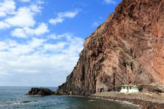 Gran Canaria cliffs. Coast and a small white home in Puerto de Sardina royalty free stock photo