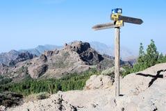 Gran Canaria, paisaje áspero, montañas, poste indicador del sendero, cielo azul Foto de archivo