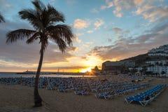 GRAN CANARIA, SPANIEN - 10. DEZEMBER 2017: Palme und sunbeds im Sonnenuntergang bei Puerto Rico Beach in Gran Canaria, Spanien Stockfotos