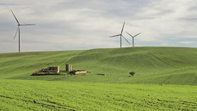 Gran cortijo abandonado rodeado rodando las colinas verdes cubiertas con los generadores de la hierba y de viento de la electrici Imágenes de archivo libres de regalías