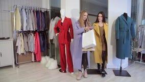 Gran día para hacer compras Dos mujeres hermosas con los panieres que caminan en la tienda de ropa almacen de metraje de vídeo