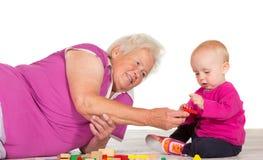 Gran, das ihr kleines Enkelkind babysitting ist stockfotos