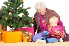 Gran e bebê que desempacotam presentes do Natal Imagem de Stock Royalty Free
