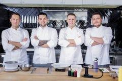 Gran equipo de cocineros que se colocan en el medio de una cocina fotografía de archivo libre de regalías