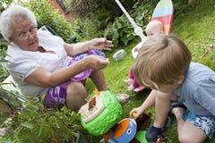 Gran et enfants de gran jouant à l'extérieur Photographie stock libre de droits