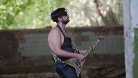 Gran funcionamiento de la guitarra en un edificio abandonado El territorio de una fábrica abandonada metrajes