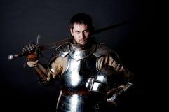 Gran guerrero con la espada y la armadura pesada imagenes de archivo
