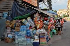 Gran número de cajas de toda clase de bebidas y de comida cerca de una pequeña tienda Botellas de agua imagen de archivo libre de regalías