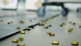 Gran número de cubiertas de la cáscara de las balas que mienten en el piso en el cuarto El tirar terrible dentro después de lo cu almacen de video