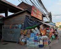 Gran numero delle scatole di tutte le specie di bevande e dell'alimento vicino ad un piccolo negozio Bottiglie di acqua immagine stock