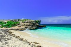 Gran opinión de invitación sobre un acantilado que se sienta en el océano y la playa tranquilos de la turquesa contra fondo mágic Imagen de archivo libre de regalías
