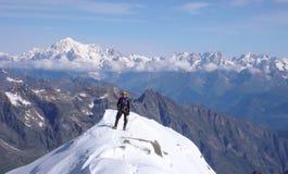 Gran Paradiso山顶的男性爬山者有勃朗峰一个巨大看法在他后的 库存照片