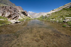 Gran Paradiso. Pond near the cross in the plain of Arolley Nivolet in Valsavaranche. In the background the Gran Paradiso (4,061 m). (Valle d'Aosta royalty free stock photography