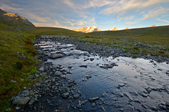 Gran Paradiso sunset. Last light illuminating the highest mountain peak in Piedmont (Italy), Gran Paradiso (4061 m), from the Rosset Creek (2700 m). Double Royalty Free Stock Image