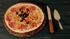 Gran pizza con los tomates al lado de un cuchillo en la tabla Timelapse almacen de video