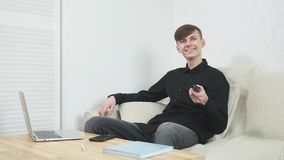Gran show televisivo Hombre joven alegre hermoso que sostiene la TV teledirigida y de observación mientras que se sienta en el so almacen de video