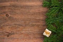 Gran-trädet förgrena sig med en gåvaask på gammal träbakgrund royaltyfri bild