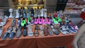 Gran variedad de calzado femenino en el mercado local, compradores que eligen los zapatos almacen de video