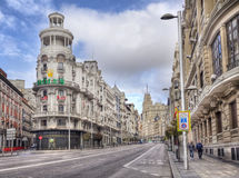 Gran Via in Madrid, Spain. Madrid, Spain - May 28, 2016: People walk along the magnificent architecture of the Gran Via main street of Madrid, Spain on May 28 royalty free stock images