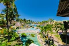 Gran vista de los argumentos del hotel, del jardín tropical y de diversas piscinas con la gente que se relaja y que nada Imagen de archivo libre de regalías