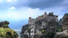 Gran vista del monasterio de Varlaam en Meteora, Thessaly, Grecia con los turistas que acometen alrededor y nubes y rayos solares almacen de metraje de vídeo