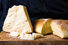 Grana Padano (parmesan cheese). Parmesan cheese with home made bread on a wooden table Royalty Free Stock Images