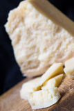 Grana Padano (parmesan cheese). Closeup of Parmesan cheese pieces on a wooden table Stock Photo