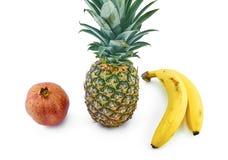 Granaatappel, ananas en bananen op wit wordt geïsoleerd dat stock foto's