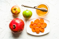 Granaatappel, appelen, wortelen en honing in het centrumwit van de lijst Stock Foto