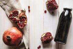 Granaatappel en flessen essentie of tint op houten rustieke lijst stock foto's