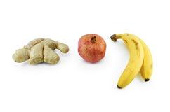 Granaatappel, gember en bananen op wit wordt geïsoleerd dat stock foto's