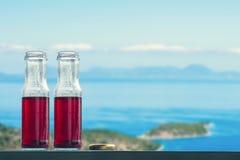Granaatappel koud sap in flessen tegenovergesteld op de eilanden en het overzees stock foto's
