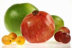 Granaatappel met andere vruchten op een witte achtergrond, intens kleurrijk en rond royalty-vrije stock fotografie