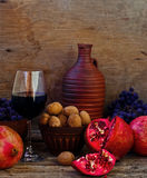 Granaatappel, okkernoten en glas wijn Stock Foto's